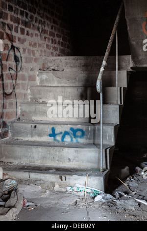 Creepy staircase in abandoned warehouse - Stock Photo