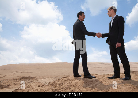 Two young businessmen shaking hands in the middle of the desert, full length - Stock Photo