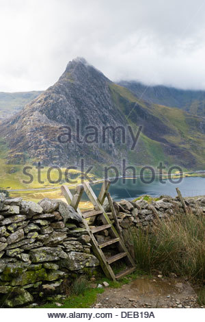 Ladder stile over a drystone stone wall with view across to Tryfan and Llyn Ogwen in Ogwen Valley on path to Carneddau - Stock Photo