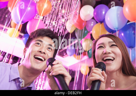 Two friends holding microphones and singing together at karaoke, balloons in the background