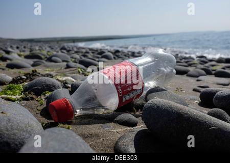 A discarded coca-cola coke soft drink  plastic bottle on Llanrhystud beach, Cardigan Bay coast, Ceredigion, west - Stock Photo