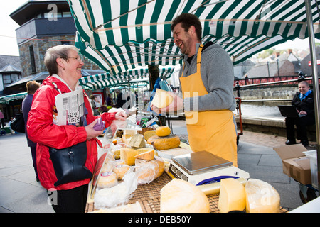 A woman buying cheese from Haverfordwest Farmers Market, Pembrokeshire. Wales UK - Stock Photo