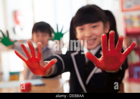 School children showing their hands covered in paint - Stock Photo