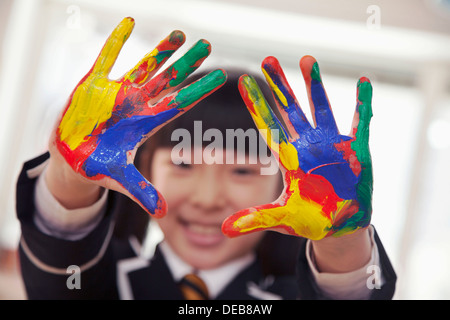 Smiling schoolgirl finger painting, close up on hands - Stock Photo
