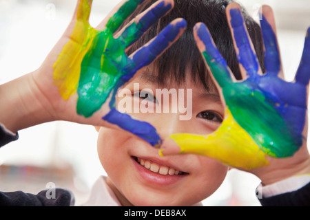 Portrait of smiling schoolboy finger painting, close up on hands - Stock Photo