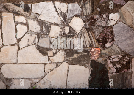 patchwork pieces of coloured marble laid in to a wall - Stock Photo