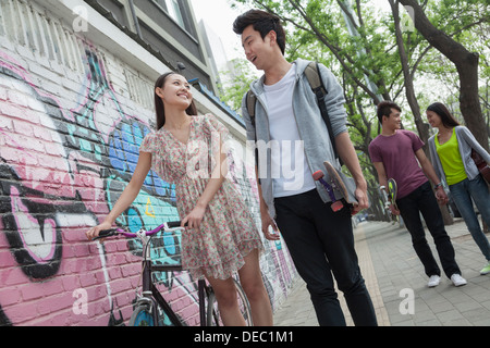 Two young couples walking down the street by a wall with graffiti, smiling and flirting with each other - Stock Photo