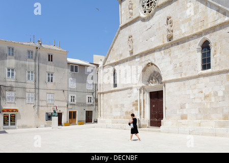Pag, Croatia, pedestrian in front of the church of Sv. Maria on the island of Pag - Stock Photo