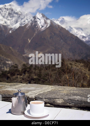 A nice cup of hot chocolate with the Himalayan mountains in the background. The peak of Mount Everest can be seen - Stock Photo