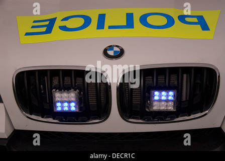 Front of BMW police car with its blue lights on, Bordon, Hampshire, UK. - Stock Photo
