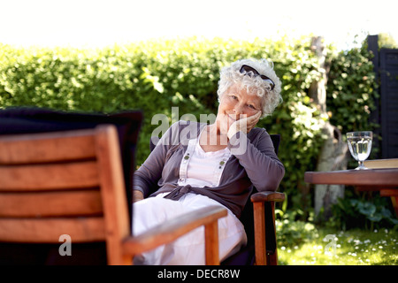 Old woman sitting on chair looking at camera. Senior female relaxing in backyard garden enjoying her retirement - Stock Photo