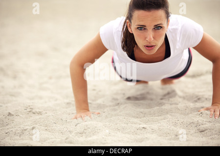 Push-ups fitness woman doing pushups outside on beach. Fit female sport model girl training crossfit outdoors. Caucasian - Stock Photo