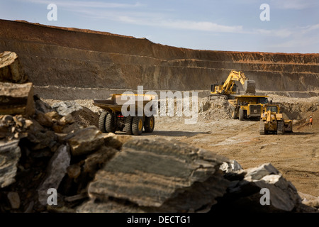 Gold mine operation in open cast surface pit with excavator and haul trucks working, Mauritania, NW Africa - Stock Photo