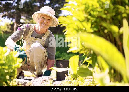 Happy elder woman with gardening tool working in her backyard garden - Stock Photo