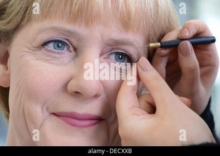 Finishing touches are applied to the face of the wax figure of Angela Merkel in the Merlin Studios, the workshops - Stock Photo