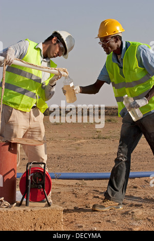 Taking water samples from bore hole, to test quality on industrial gold mining complex, Mauritania, NW Africa - Stock Photo