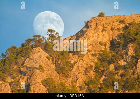 Real full moon rising over Puig des Teix mountain at sunset. Tramuntana mountains, Deia, Majorca, Balearic islands, Spain