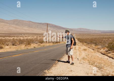 Man hitchhiking on a rural desert road - California USA - Stock Photo