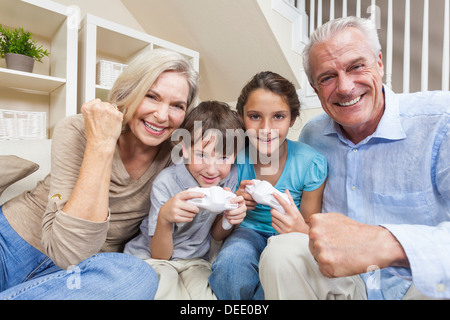 Senior adults & children, grandparents, grandson & granddaughter, family having fun playing video console games - Stock Photo