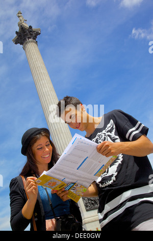 Young couple looking at map with Nelson's Column behind, Trafalgar Square, London, England, United Kingdom, Europe - Stock Photo
