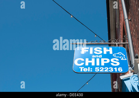 fish and chip sign outside a fish and chip shop - Stock Photo