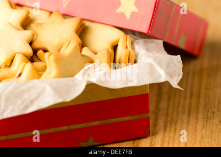 Christmas cookies star in red decoration box Xmas tin - Stock Photo