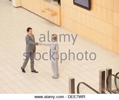 Business people standing at bottom of escalator - Stock Photo