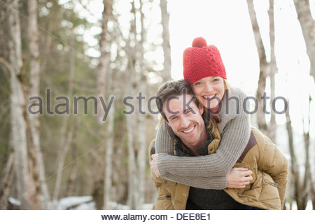 Portrait of smiling couple piggybacking in woods - Stock Photo