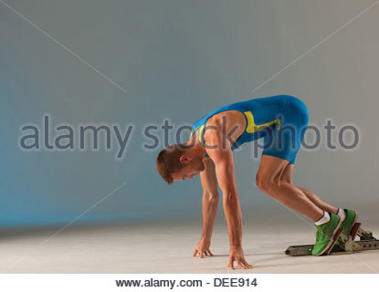 Athlete in starting blocks - Stock Photo