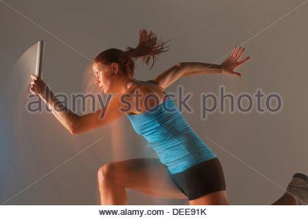 Blurred view of runner carrying baton - Stock Photo