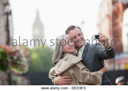 Couple taking self-portrait with digital camera in city - Stock Photo