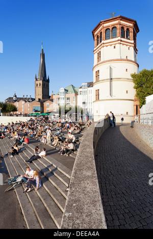 People on stairs by the Rhine, Lambertus Church and Schlossturm tower, Dusseldorf, North Rhine Westphalia, Germany, - Stock Photo