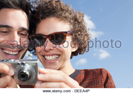 Happy couple taking self-portrait with digital camera in front - Stock Photo