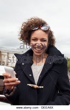 Woman holding cell phone on double decker bus below monument - Stock Photo