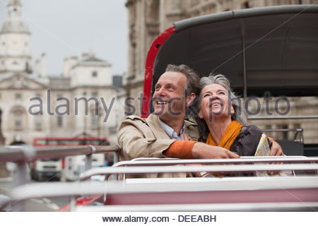 Smiling couple looking up on double decker bus in London - Stock Photo