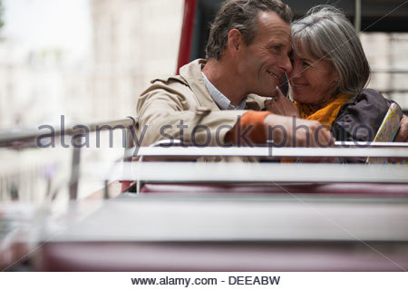 Smiling senior couple on double decker bus in London - Stock Photo
