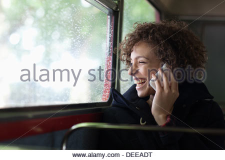 Happy woman talking on cell phone on bus - Stock Photo
