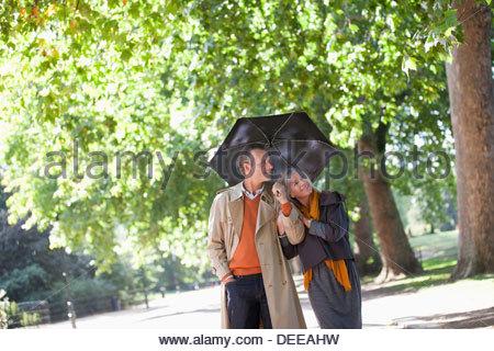Couple sharing umbrella in sunny park - Stock Photo