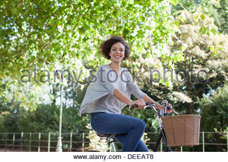 Portrait of smiling woman riding bicycle in park - Stock Photo