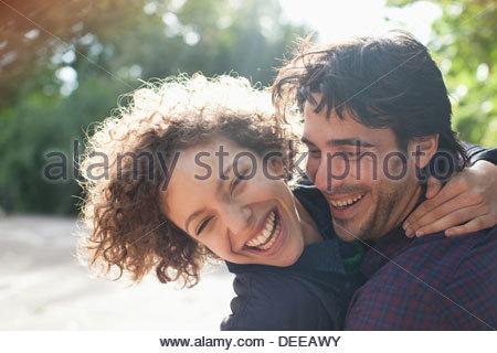Sun shining behind happy couple hugging - Stock Photo