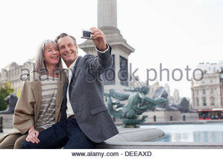 Couple taking self-portrait with digital camera under monument - Stock Photo