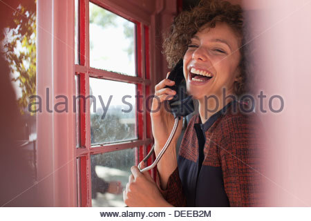 Portrait of smiling woman using telephone booth - Stock Photo