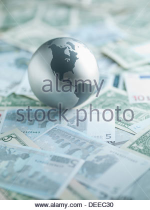 Metal globe resting on paper currency - Stock Photo