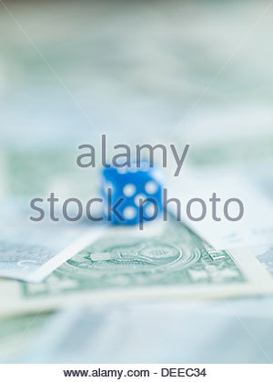 Blur blue dice on pile of dollar bills - Stock Photo