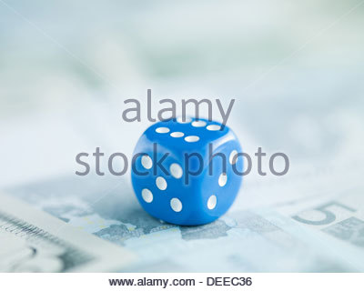 Blue dice on pile of dollar bills - Stock Photo