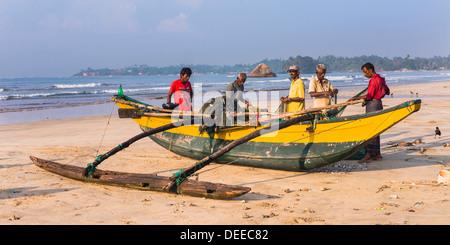 Fishermen sorting their catch on Weligama Beach, South Coast of Sri Lanka, Asia - Stock Photo