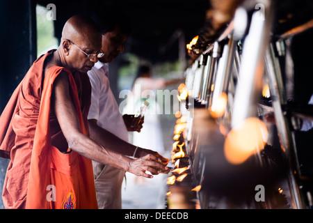 Buddhist monk praying at Sri Maha Bodhi in the Mahavihara (The Great Monastery), Anuradhapura, Sri Lanka, Asia - Stock Photo