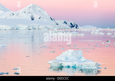 Sunset over icebergs in the Gerlache Strait, Antarctica, Southern Ocean, Polar Regions - Stock Photo