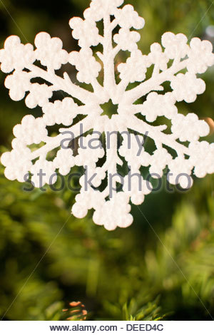 Snowflake Christmas ornament on tree - Stock Photo