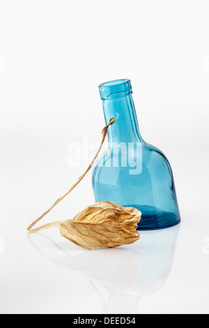Curled dry leaf and blue glass bottle - Stock Photo